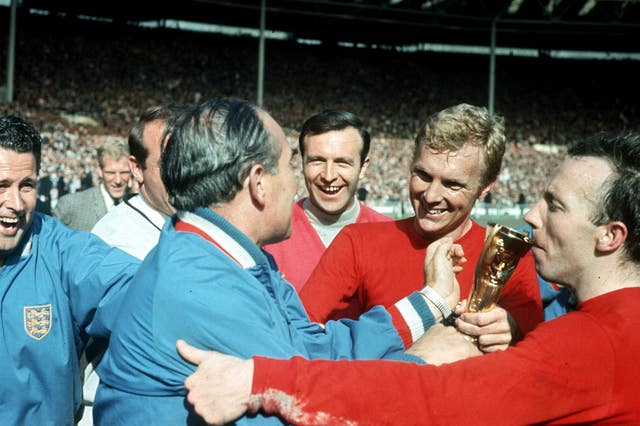 Stiles kisses the World Cup trophy, held by Sir Alf Ramsey