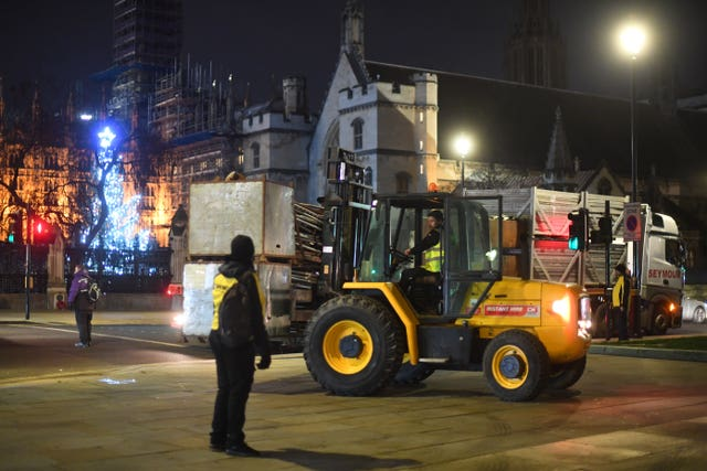 Construction workers put up fencing around the statues in Parliament Square