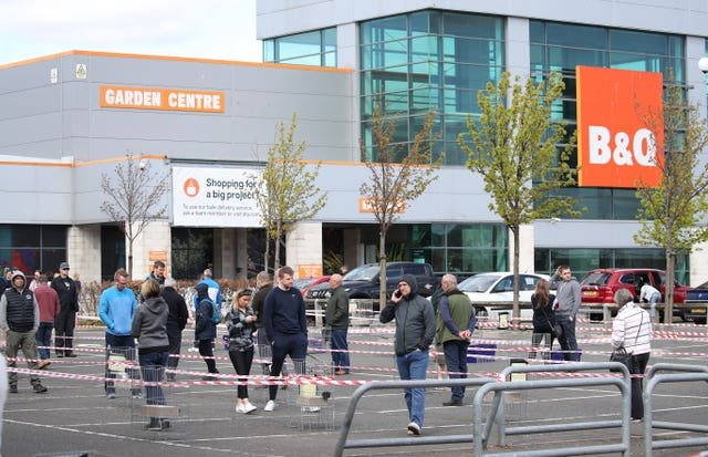 Members of the public follow social distancing guidelines and queue in the car park of B&Q