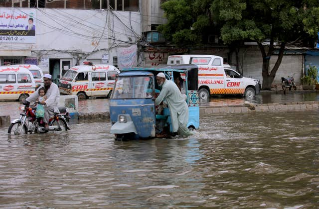 A driver pushes his motorised rickshaw through a flooded road after heavy monsoon rains in Karachi, Pakistan