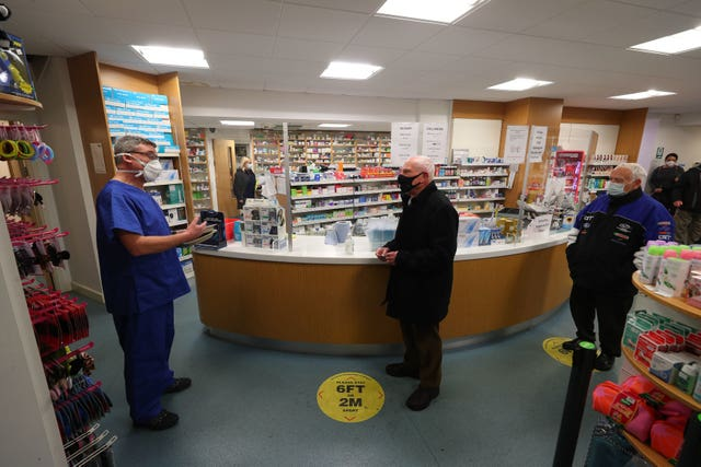 Pharmacist Andrew Hodgson (left) speaks to Robert Salt (centre), 82, before he receives an injection of the coronavirus vaccine at Andrews Pharmacy in Macclesfield