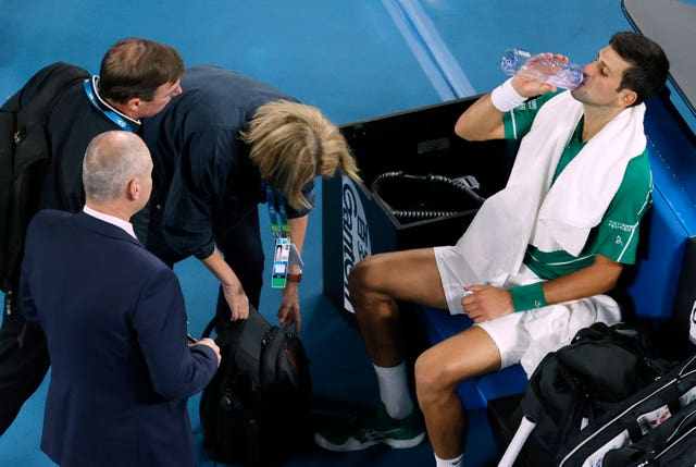 Novak Djokovic is attended to by medical staff during the final