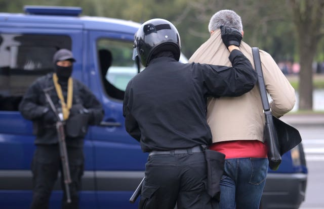 Police detain a man during a protest