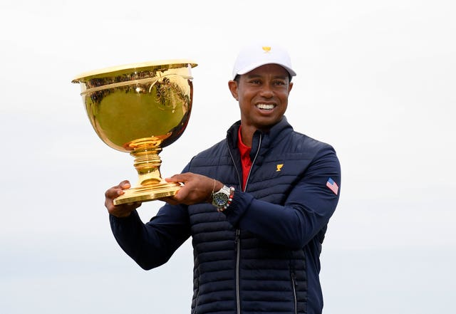 Tiger Woods holds up the Presidents Cup trophy after victory for the US team