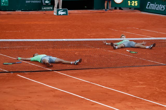 Germany's Kevin Krawietz, right, and Andreas Mies, left, lie flat on the court after winning the men's doubles title