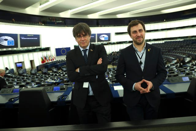 Catalonia's former regional president Carles Puigdemont, left, and former Catalan regional minister Antoni Comin stand in the plenary hemicycle of the European Parliament in Strasbourg
