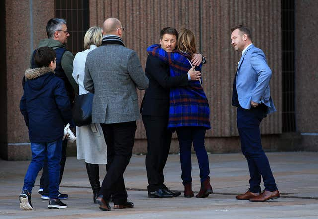 Steve Walters hugs a friend after the verdict while fellow Bennell victims Chris Unsworth (fourth left) and Micky Fallon look on (Peter Byrne/PA)