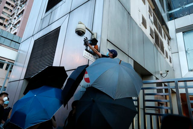 A protester spray-paints the CCTV camera outside the Chinese Liaison Office