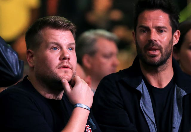 Television personality James Corden, left, and footballer turned broadcaster Jamie Redknapp watch from ringside