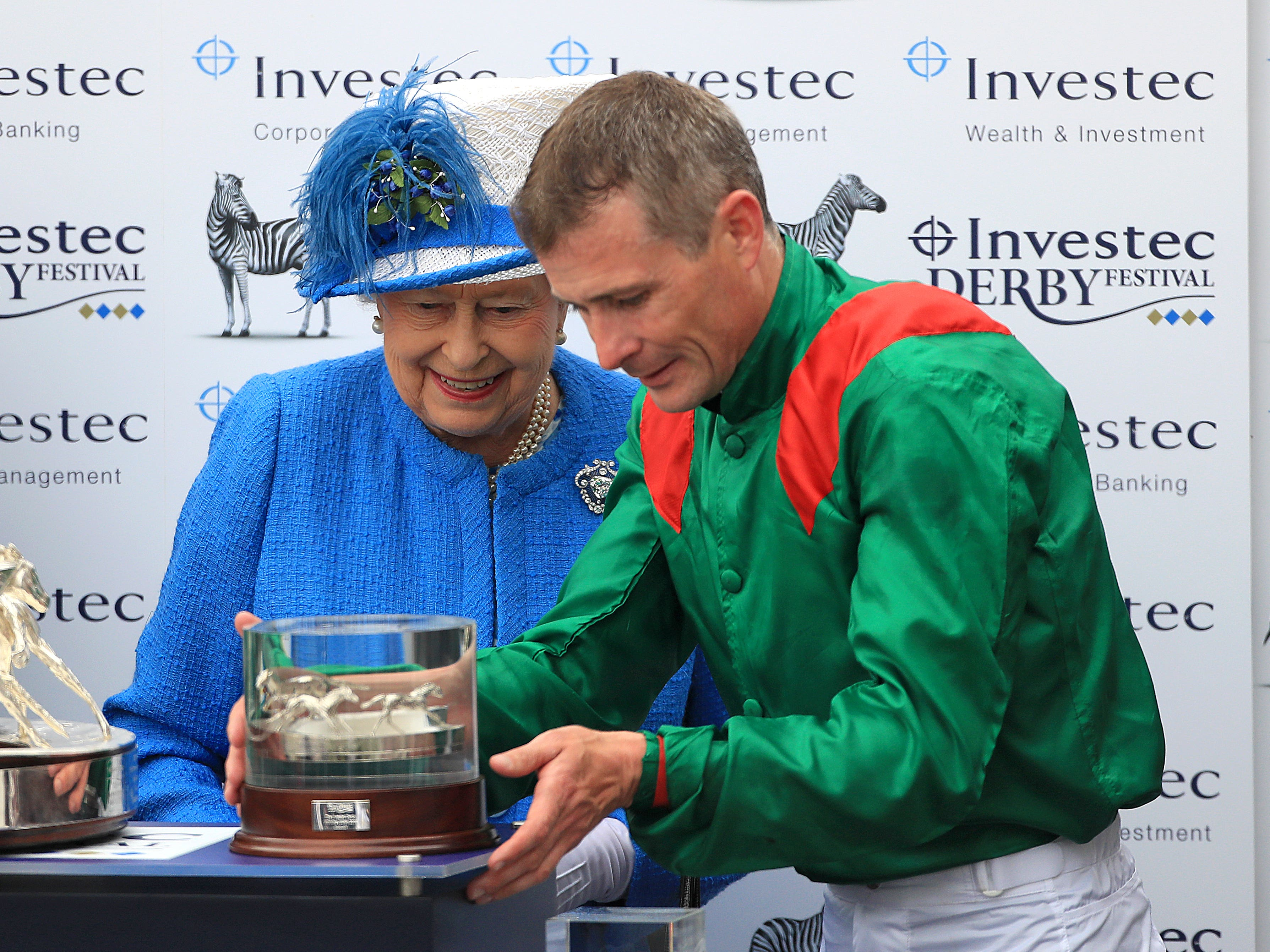 Pat Smullen is presented with his trophy for winning the Derby by the Queen (David Davies/PA)