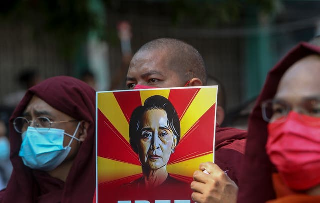 Buddhist monks display pictures of deposed leader Aung San Suu Kyi  (AP)