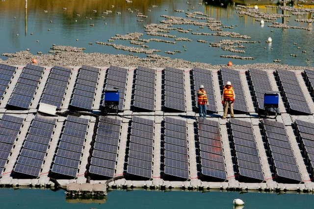 Workers stand on a floating island of solar panels