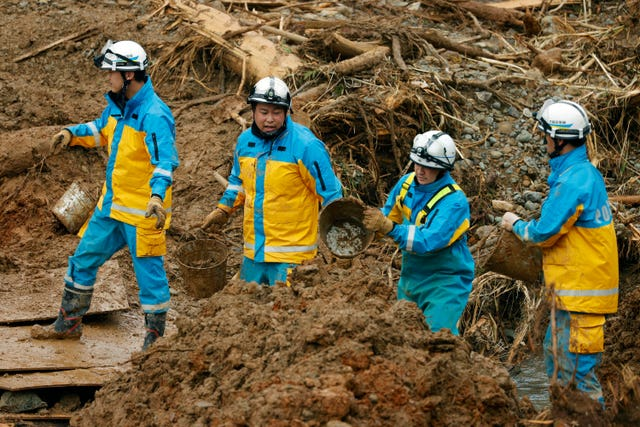 Police officers carry earth and sand by buckets as they search for the missing in Tsunagi town, Kumamoto prefecture, southern Japan (Kyodo News/AP)