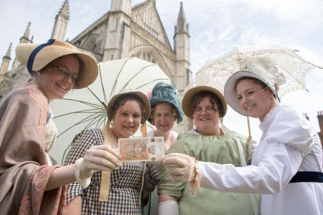 Jane Austin enthusiasts hold the new £10 note outside Winchester Cathedral, which marks the 200th anniversary of Austen's death, during its unveiling at the cathedral (PA)