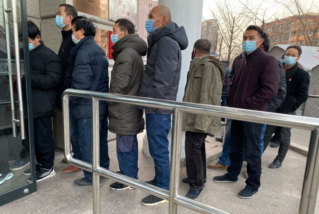 Locals line up for vaccinations in Beijing (Ng Han Guan/AP)