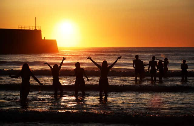Swimmers had a great view of the stunning sunrise as they braved the cold (Jane Barlow/PA)