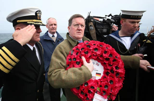Lord George Robertson holds a wreath prior to throwing it in the sea close to the wreck of SS Tuscania (PA/Jane Barlow)