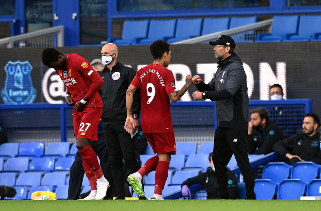 Liverpool manager Jurgen Klopp fistbumps Roberto Firmino as he is replaced by Divock Origi