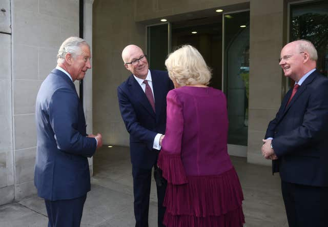The Prince of Wales and Duchess of Cornwall are greeted by Clive Marshall, chief executive of the PA Group and chairman Murdoch MacLennan (Yui Mok/PA)