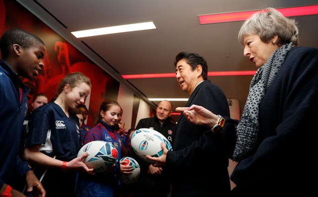 Mrs May and Mr Abe chatting to school children at the stadium