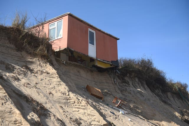 A partially-collapsed house sits on the cliff edge at The Marrams in Hemsby (Joe Giddens/PA)