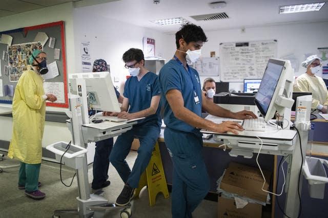Staff members work at a desk in the ICU
