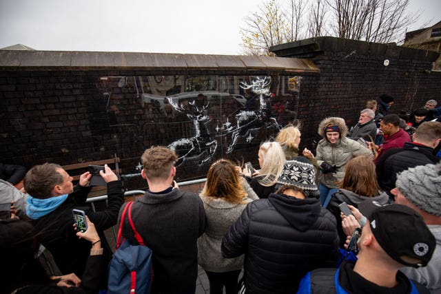 Workmen use perspex sheeting to protect a new Banksy artwork in Birmingham's Jewellery Quarter