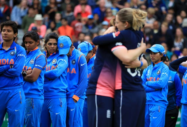 India's dejected players look on as England celebrate winning the women's cricket World Cup in 2017. The hosts completed a stunning fightback to triumph by nine runs. Seamer Anya Shrubsole finished with 6-46 - the best figures in a World Cup final - as India were bowled out for 219 with eight balls unused