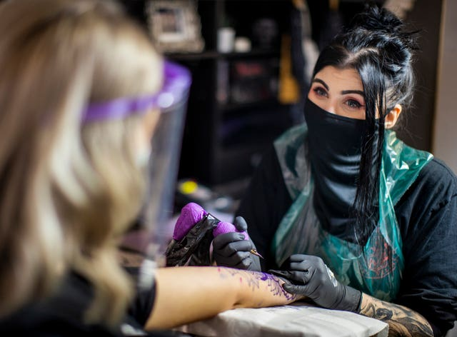 Tattoo artist Kirsty Mick (right) tattooing customer Chloe McEnhill at Belfast City Skinworks, as tattoo parlours in Northern Ireland are allowed to reopen as lockdown eases