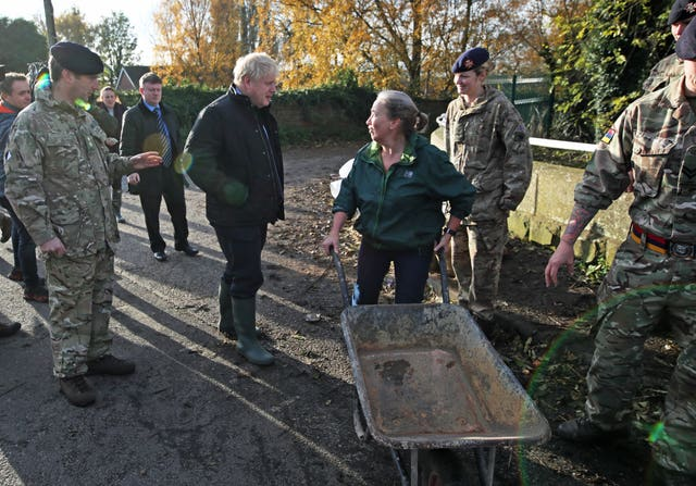 Boris Johnson talks with a local woman pushing a wheelbarrow during a visit to Stainforth