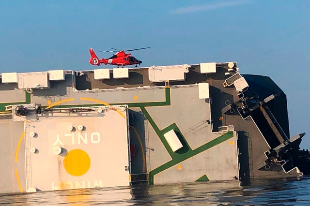 A US Coast Guard helicopter hovers over the ship in St Simons Sound