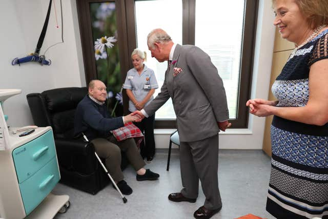 The prince spoke to patient John Black before unveiling a plaque marking Omagh Hospital and Primary Care Complex's official opening (Niall Carson/PA)
