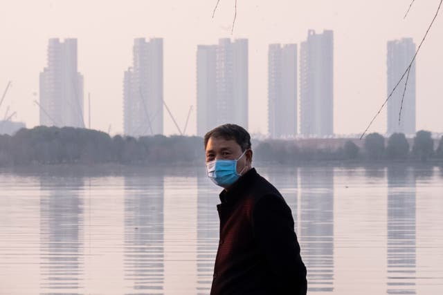 A man wears a face mask as he stands along the waterfront in Wuhan in central China's Hubei Province