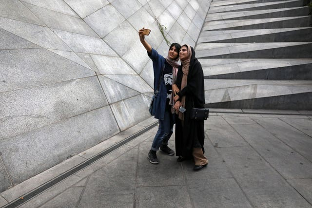 Two Iranian women take a selfie outside a shopping centre in northern Tehran