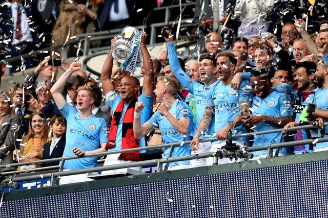 Vincent Kompany lifts the FA Cup after Manchester City complete a domestic treble with a 6-0 rout of Watford at Wembley