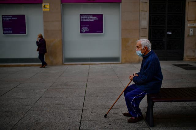 An elderly man sits on a bench wearing a face mask to protect against coronavirus, in Pamplona, northern Spain (Alvaro Barrientos/AP)