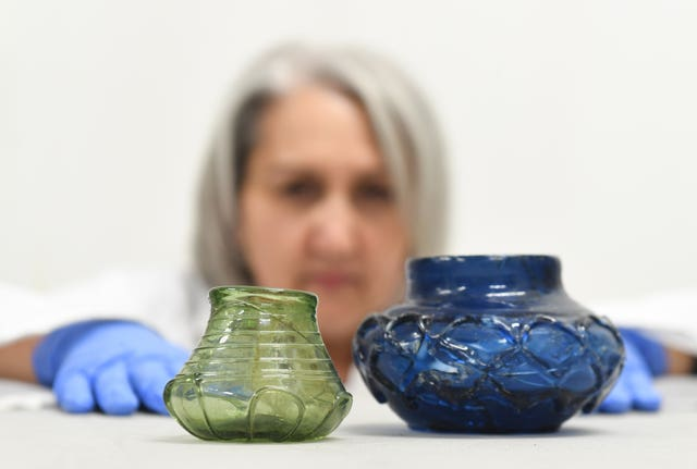 Conservator Claire Reed inspects decorated glass beakers found at the site