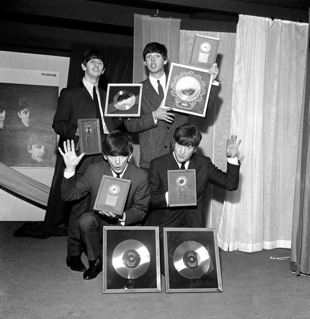 The Beatles pictured with silver discs awarded for sales of their albums Please Please Me and With the Beatles. (Image: PA)