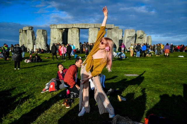 A woman performs yoga at Stonehenge