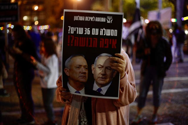 A woman holds a poster of Benjamin Netanyahu, right, and Benny Gantz, that reads, 'a government with 36 ministers? Where is the shame?'