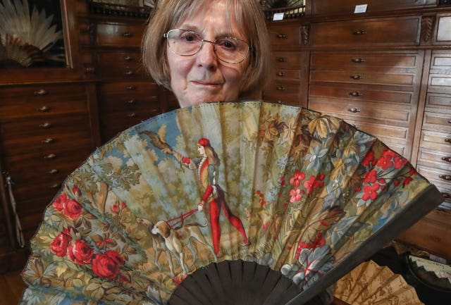Anne Hoguet, 74, fan maker and director of the hand fan-making museum poses with a wood roasted hand fan representing a falcon hunt, gouache painting g on paper from 1880 at the museum in Paris, Wednesday, Jan. 20, 2021. Just like the leaves of its gilded fans, France's storied hand fan-making museum could fold up and vanish. The splendid Musee de l'Eventail in Paris, a classed historical monument, is the culture world's latest coronavirus victim