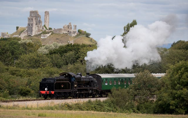 The SR U Class steam locomotive 31806 passes Corfe Castle on the Swanage Railway, as it travels between Norden and Swanage (Andrew Matthews/PA)