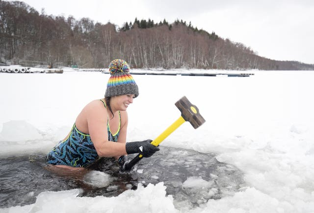 Alice Goodridge, from Newtonmore, uses a sledgehammer to create a channel in the ice to swim in Loch Inch, in the Cairngorms National Park