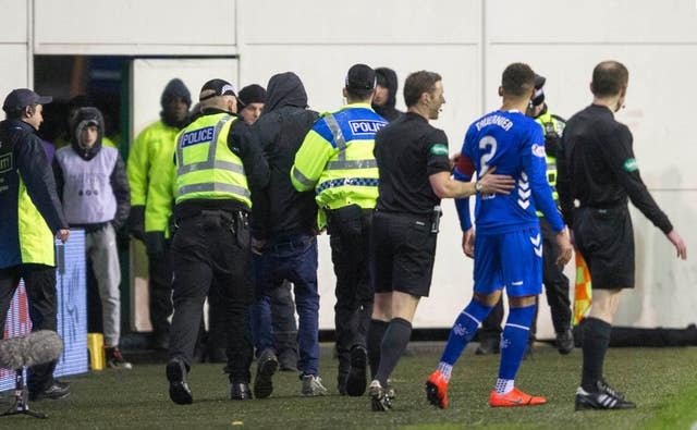 Rangers James Tavernier is pulled away from a fan that ran on to the pitch at Hibernian
