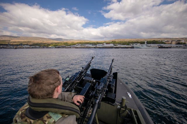 A Royal Marine patrols the waters at HMNB Clyde, which is the home of HMS Vigilant, the Vanguard-class submarine carries the UK's Trident nuclear deterrent