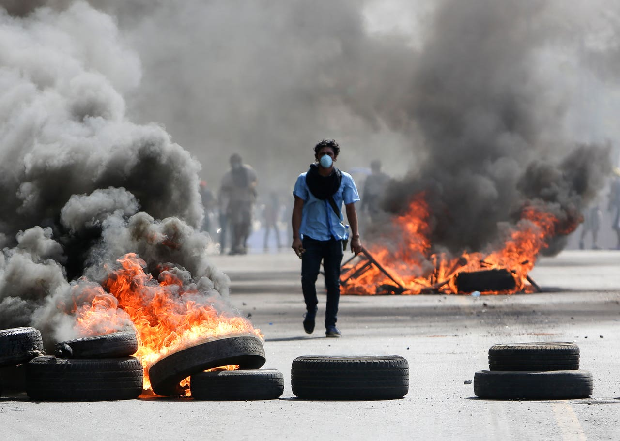 A masked protester walks between burning barricades in Managua (Alfredo Zuniga/AP)