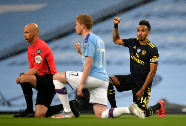 Arsenal's Pierre-Emerick Aubameyang, right, and Manchester City's Kevin De Bruyne, take the knee after the kick-off of their Premier League match on Wednesday
