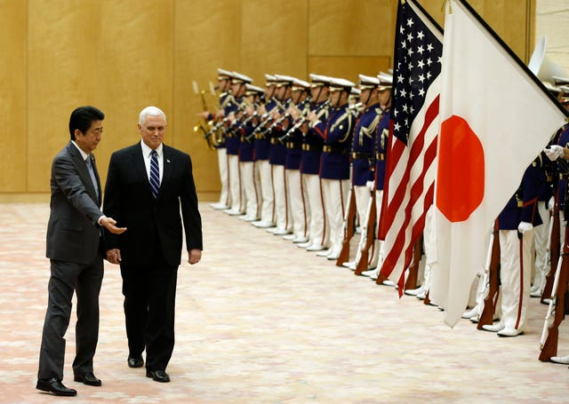 Mike Pence and Shinzo Abe review an honour guard in Japan  (Toru Hanai/AP)