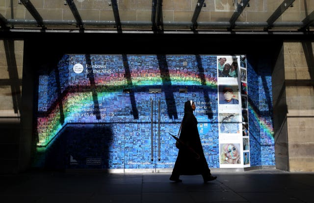 A woman walks past a Rainbows for the NHS mosaic made up of thousands of pictures and stories, submitted during the ongoing pandemic, which covers the windows and entrance to the Buchanan Galleries in central Glasgow, some six months on from the evening of March 23 when Prime Minister Boris Johnson announced nationwide restrictions