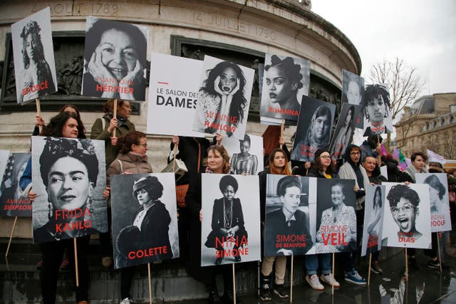 Women hold posters of famous feminists in Paris, France (Michel Euler/AP)
